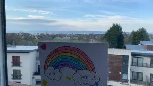 A picture of a rainbow in a window, with the Edinbrugh skyline behind it.