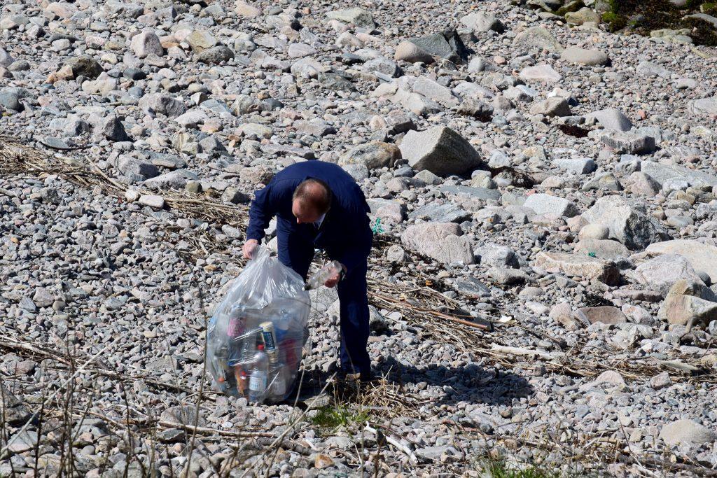 Colleague picking up litter on beach